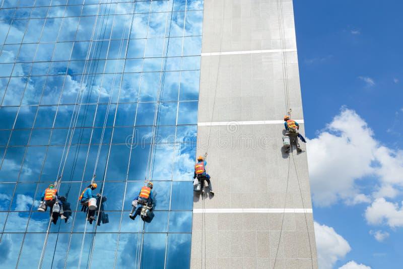 Arbeiders die de dienst van de venstersspiegel bij de hoge stijgingsbouw schoonmaken stock foto's