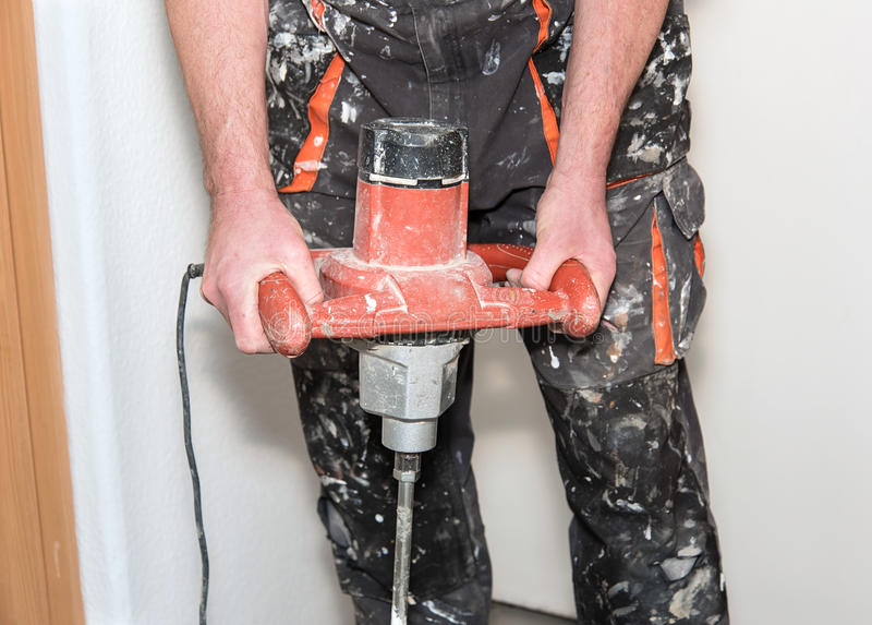 Arbeiders die de kleefstof in bouw mengen stock foto