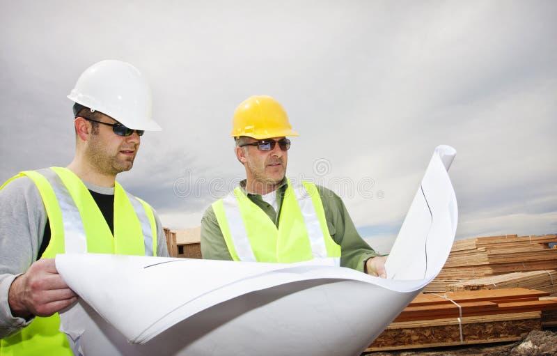 Arbeiders die de Plannen van de Bouw lezen royalty-vrije stock foto's