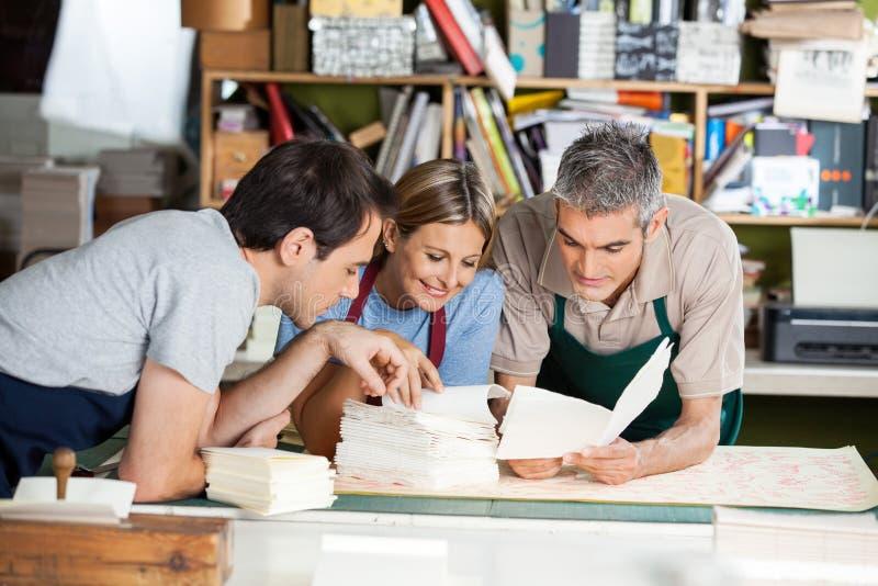 Arbeiders die Documenten samen in Fabriek analyseren royalty-vrije stock afbeelding