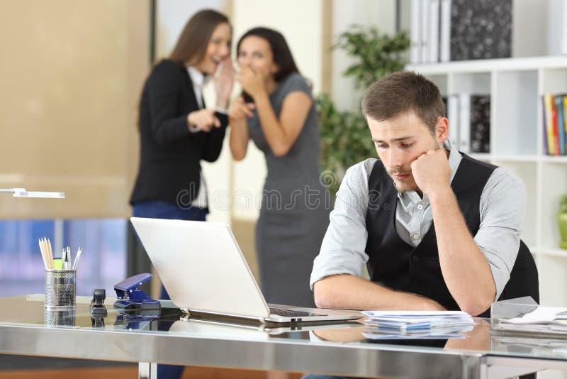 Arbeiders die een collega intimideren op kantoor stock fotografie