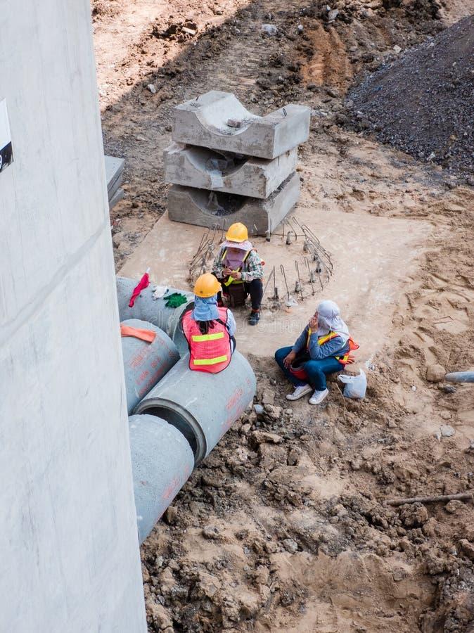 Arbeiders die een rust nemen bij bouwwerf stock foto