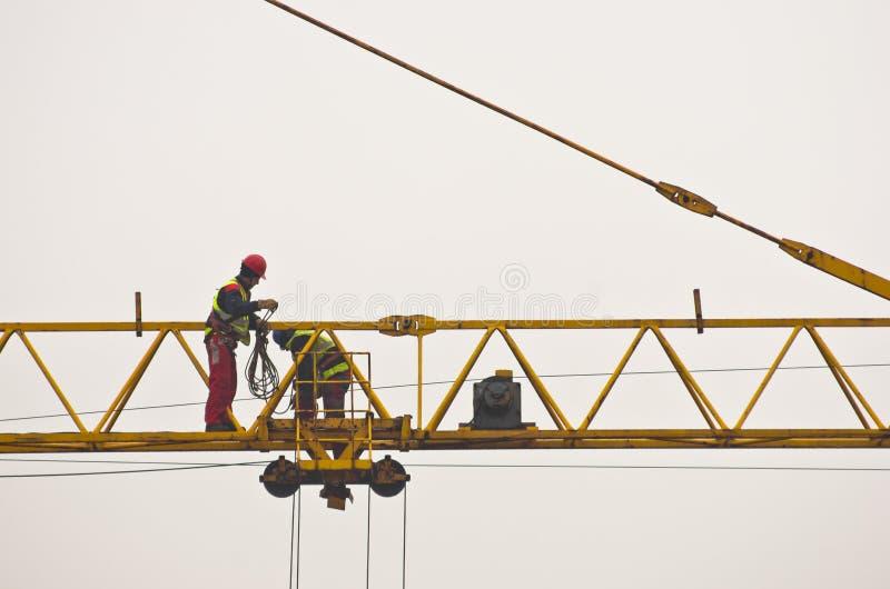 Arbeiders die en een grote bouwkraan in Belgrado inspecteren onderhouden stock fotografie