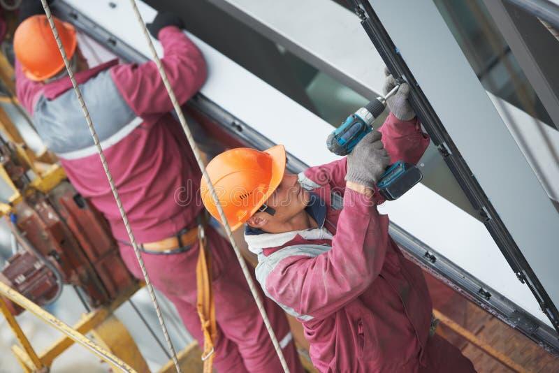Arbeiders die glasvenster installeren bij de bouw stock afbeeldingen