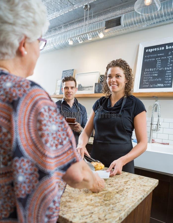 Arbeiders die Hogere Vrouw in Cafetaria bekijken stock foto's