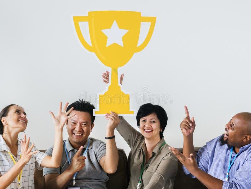 Arbeiders die hun succes met een trofee vieren royalty-vrije stock foto