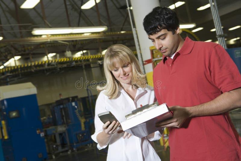 Arbeiders die in Krantenfabriek werken stock foto's