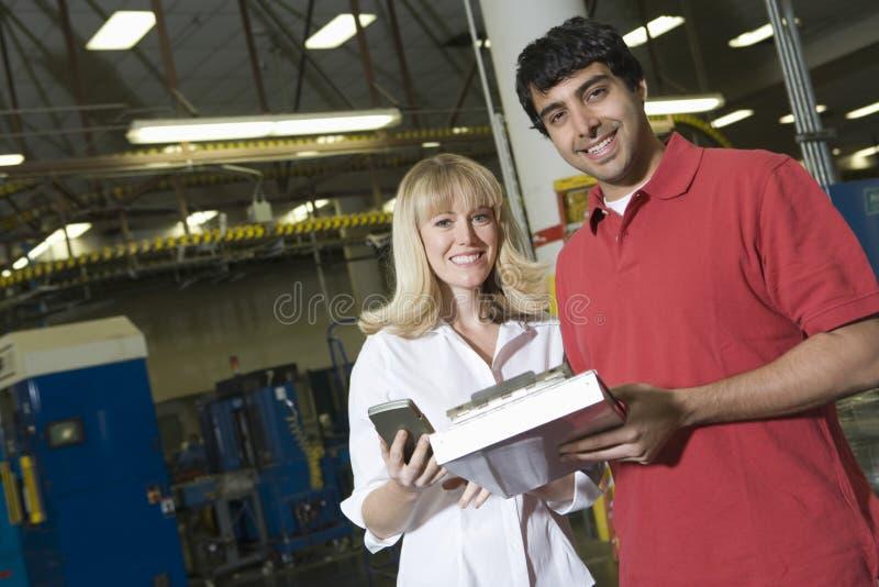 Arbeiders die in Krantenfabriek werken stock fotografie