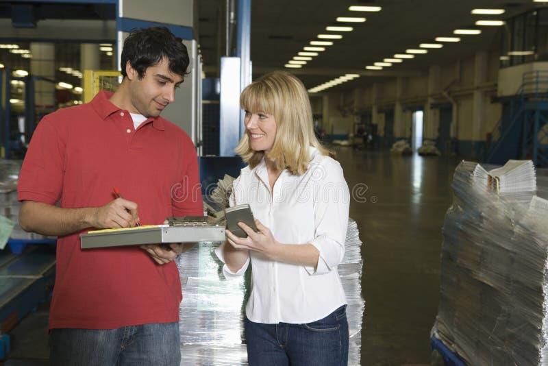 Arbeiders die in Krantenfabriek werken stock afbeelding