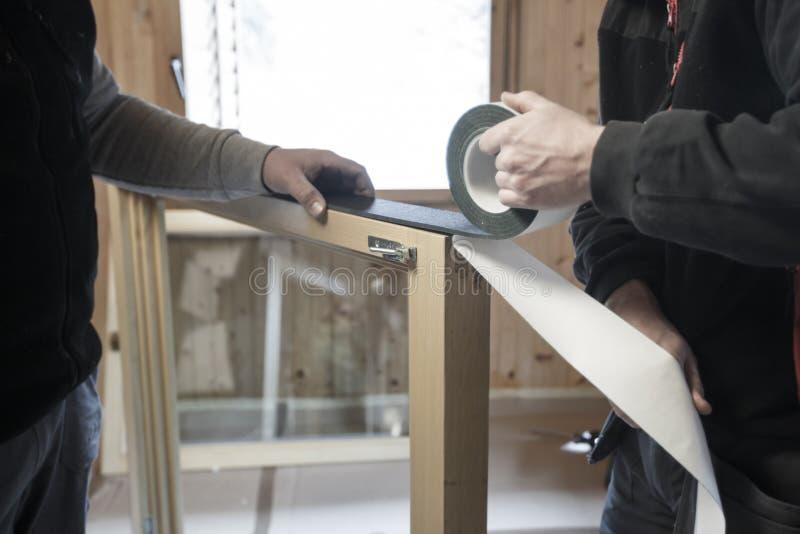 Arbeiders die nieuwe vensters installeren stock foto's