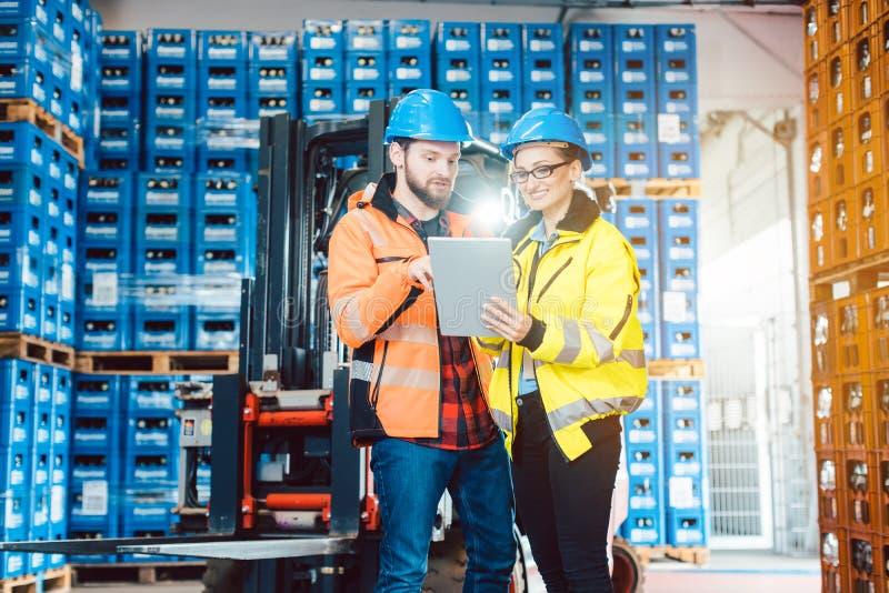 Arbeiders die in pakhuis gegevens over tabletcomputer controleren stock afbeelding