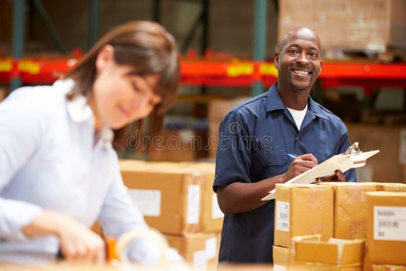 Arbeiders die in Pakhuis Goederen voor Bericht voorbereiden stock afbeelding