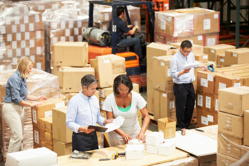Arbeiders die in Pakhuis Goederen voor Bericht voorbereiden stock afbeeldingen
