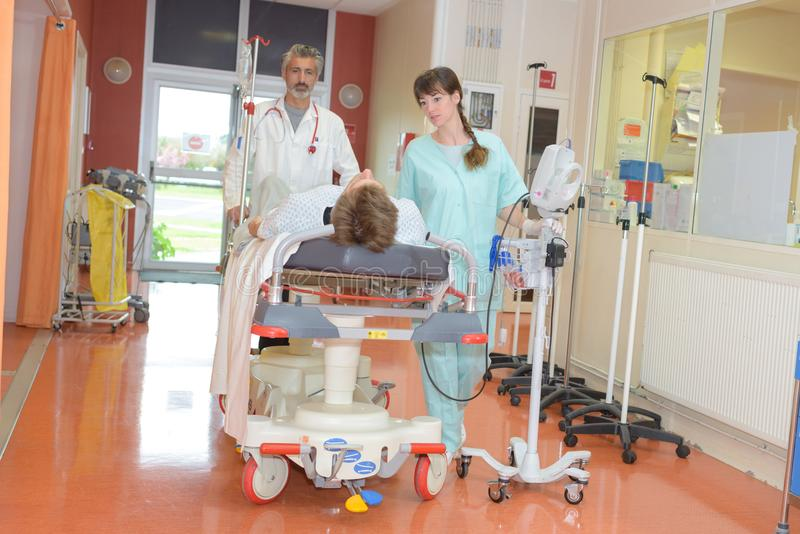 Arbeiders die patiënten in het ziekenhuis bewegen stock afbeelding