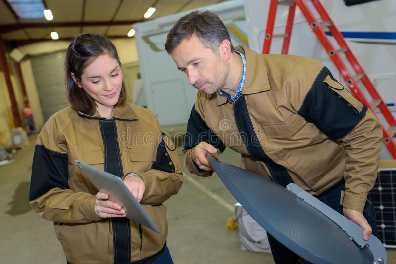 Arbeiders die satellietschotel en tabletcomputer houden stock afbeeldingen