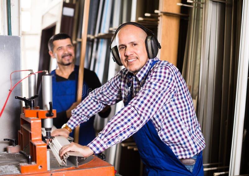 Arbeiders die vensterprofielen snijden royalty-vrije stock afbeeldingen
