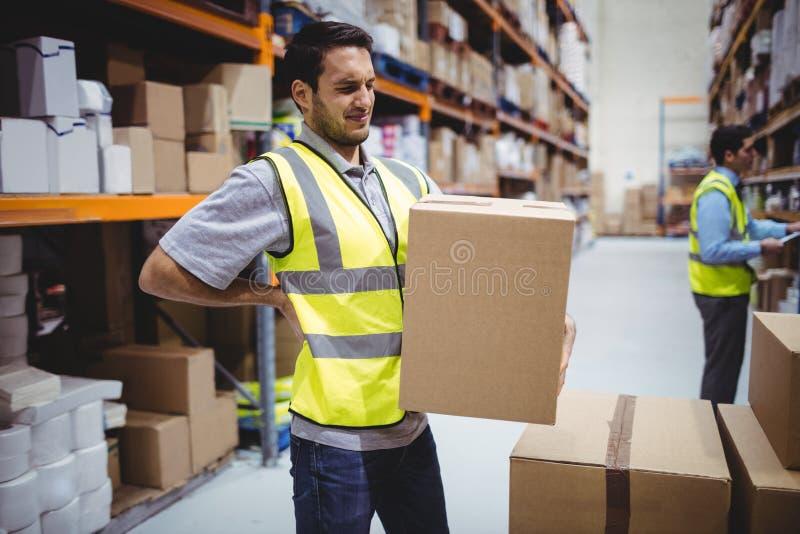 Arbeiders dragende doos met rugpijn royalty-vrije stock fotografie