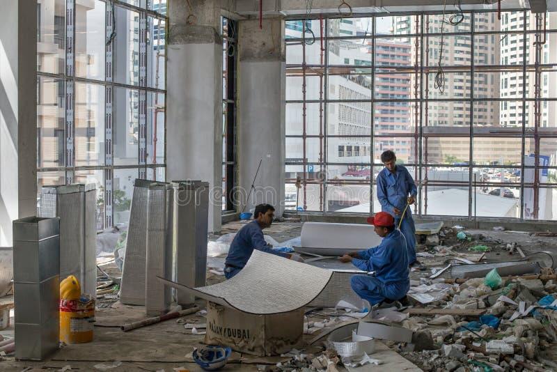 Arbeiders in een contructionplaats in Doubai stock fotografie