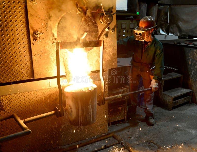 Arbeiders in een gieterij die een metaalwerkstuk gieten - veiligheid op het werk en groepswerk royalty-vrije stock fotografie