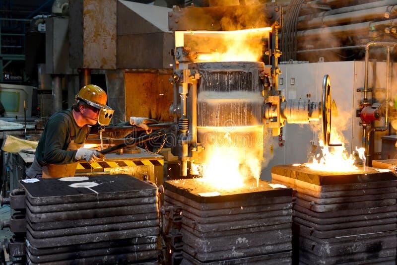 Arbeiders in een gieterij die een metaalwerkstuk gieten - veiligheid op het werk en groepswerk stock foto's