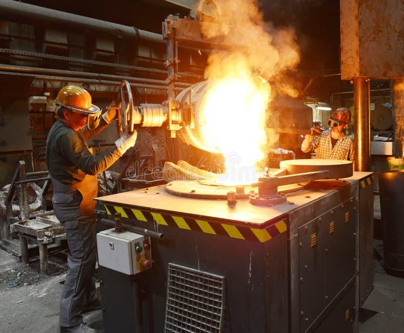 Arbeiders in een gieterij die een metaalwerkstuk gieten - veiligheid op het werk en groepswerk stock foto