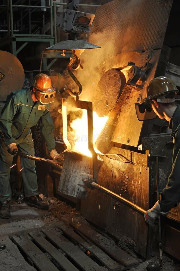 Arbeiders in een gieterij die een metaalwerkstuk gieten - veiligheid op het werk en groepswerk royalty-vrije stock afbeelding