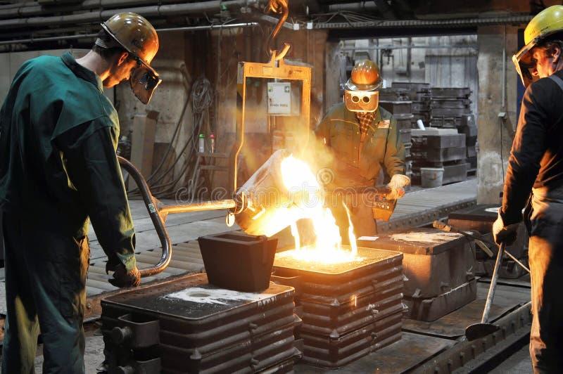 Arbeiders in een gieterij die een metaalwerkstuk gieten - veiligheid op het werk en groepswerk stock afbeelding