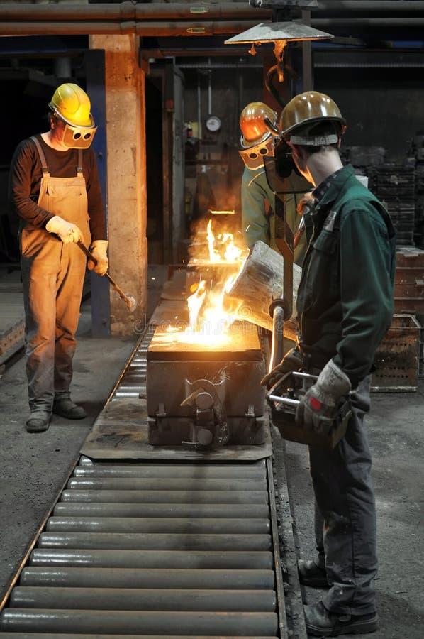 Arbeiders in een gieterij die een metaalwerkstuk gieten - veiligheid op het werk en groepswerk royalty-vrije stock afbeeldingen
