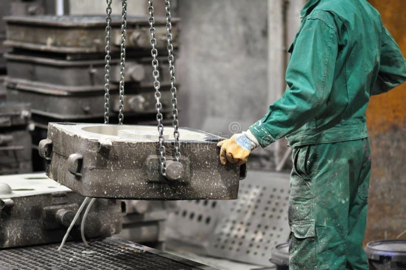 Arbeiders in een gieterij die een metaalwerkstuk gieten - veiligheid op het werk en groepswerk stock fotografie