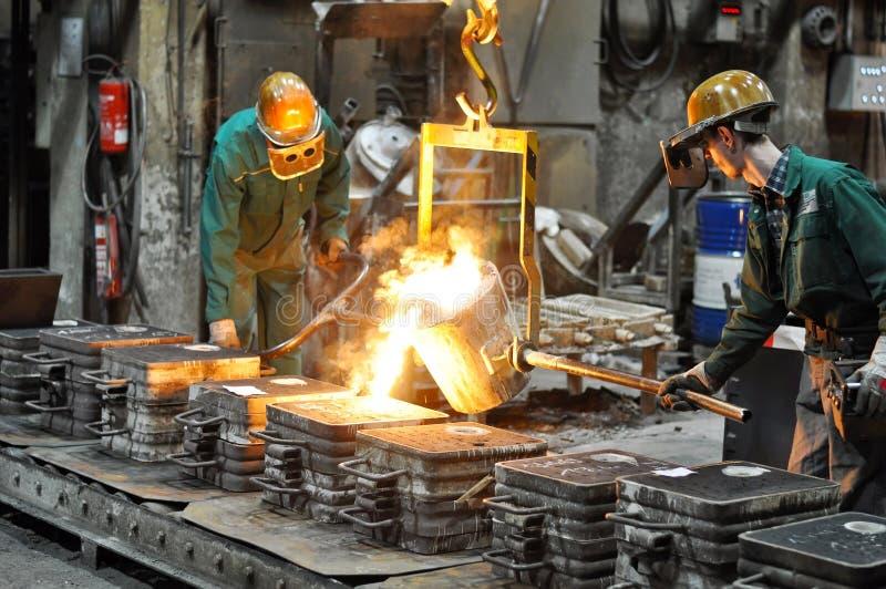 Arbeiders in een gieterij die een metaalwerkstuk gieten - veiligheid op het werk en groepswerk royalty-vrije stock foto's