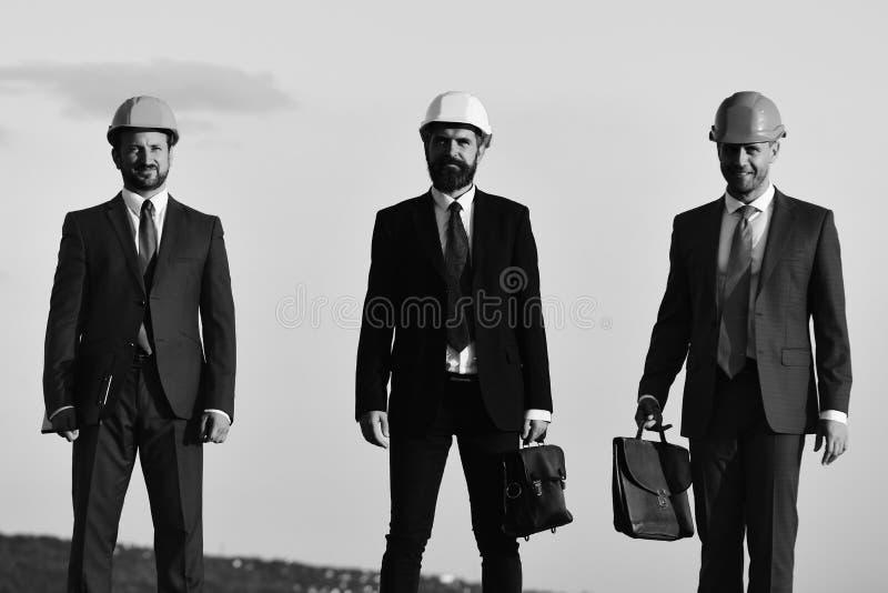 Arbeiders en ingenieursgreepvergadering in openlucht Coworking en bouwvakconcept Voormannen huidig groepswerk stock fotografie