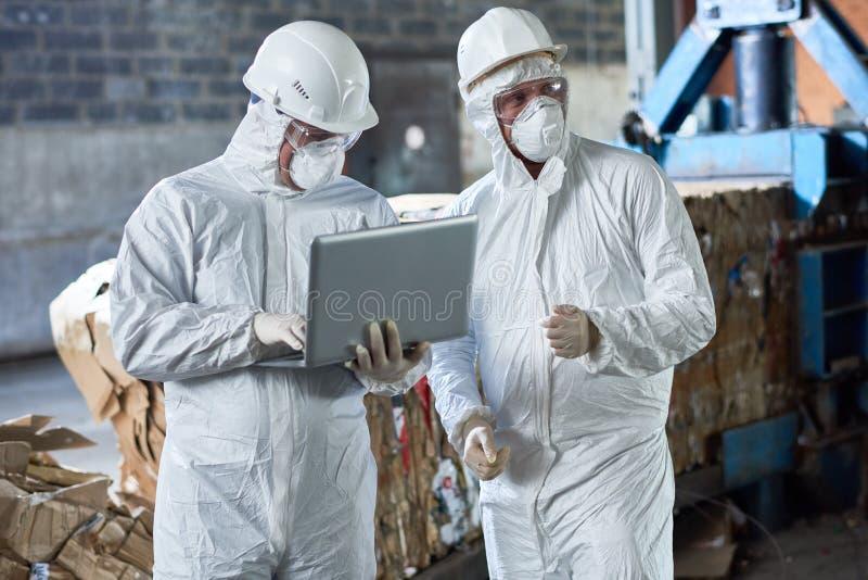 Arbeiders in Hazmat-Kostuums bij Moderne Recyclingsfabriek royalty-vrije stock afbeeldingen