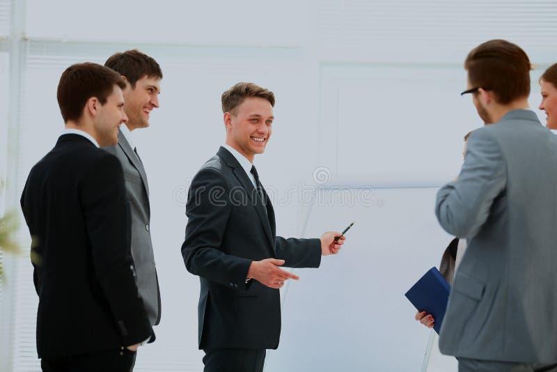 Arbeiders op commerciële vergadering die presentatie van financiële verslagen in modern bureau bekijken stock foto's