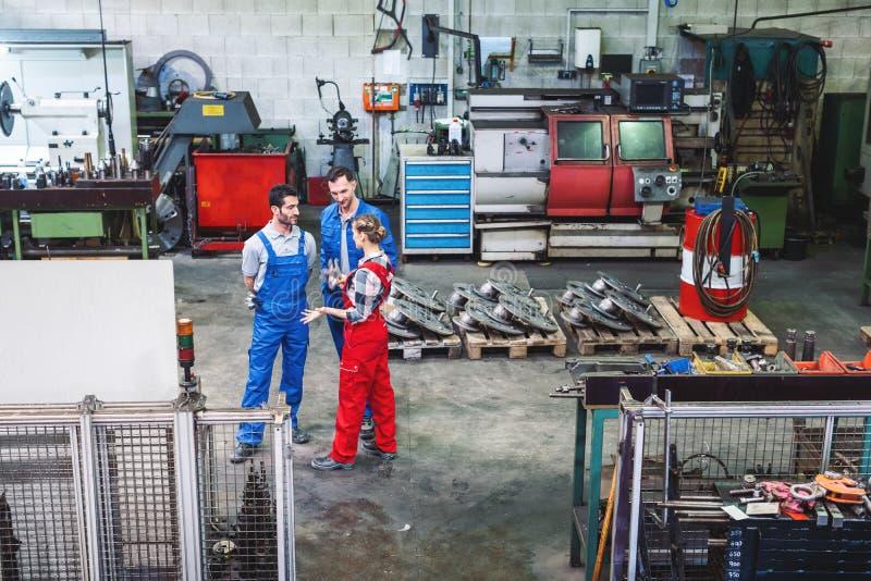 Arbeiders op de fabrieksvloer in bespreking royalty-vrije stock afbeeldingen