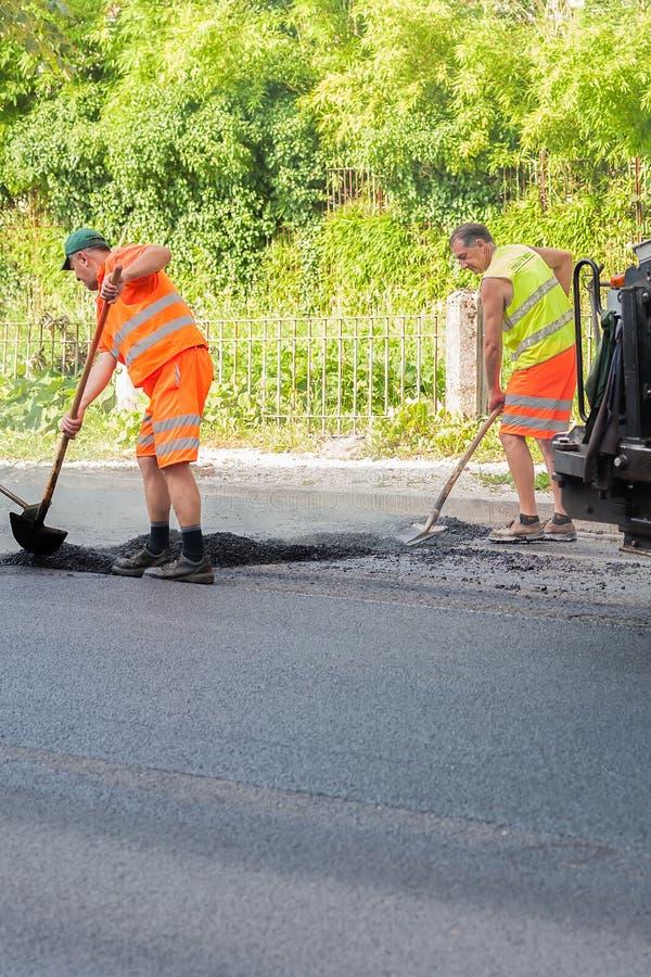 Arbeiders op een wegenbouw, de industrie en groepswerk stock afbeelding