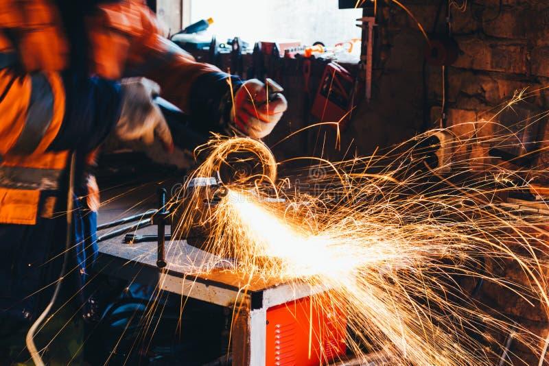 Arbeiders scherp metaal met molen in zijn workshop Vonkt terwijl het malen van ijzer stock afbeeldingen