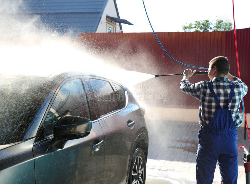Arbeiders schoonmakende auto met de straal van het hoge drukwater royalty-vrije stock afbeeldingen