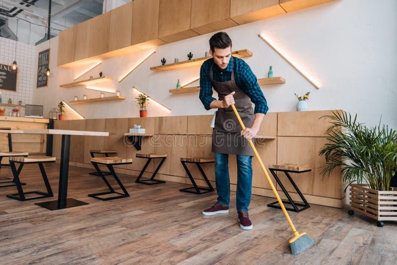 Arbeiders schoonmakende vloer met bereik stock foto