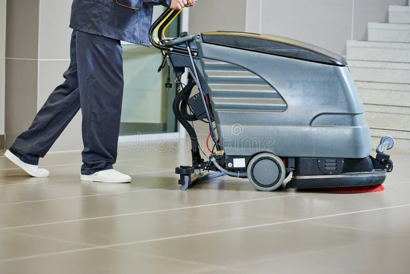 Arbeiders schoonmakende vloer met machine stock afbeelding