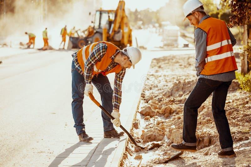 Arbeiders in weerspiegelende vesten die schoppen met behulp van tijdens rijweg wor stock fotografie