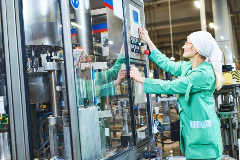 Arbeiders werkende transportband of etiketteringsmachine bij fabriek stock afbeelding