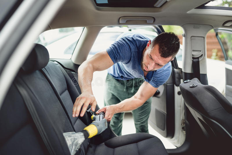 arbeiders zuigende en schoonmakende auto Autozorg en het detailleren van concept stock foto