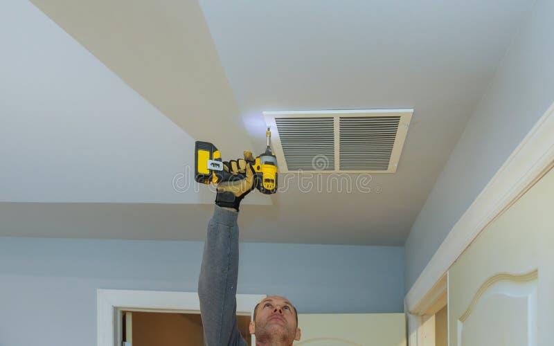arbeidersbouwer die de geventileerde bouw van de ventilatiedekking van de bouw installeren stock afbeelding