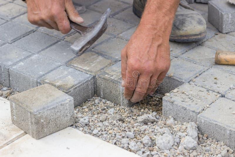 Arbeidershanden die concrete baksteenbetonmolens 2 leggen stock afbeelding