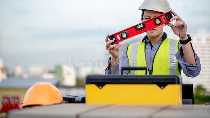 Arbeidersmens die het rode hulpmiddel van het aluminiumwaterpas houden royalty-vrije stock afbeeldingen