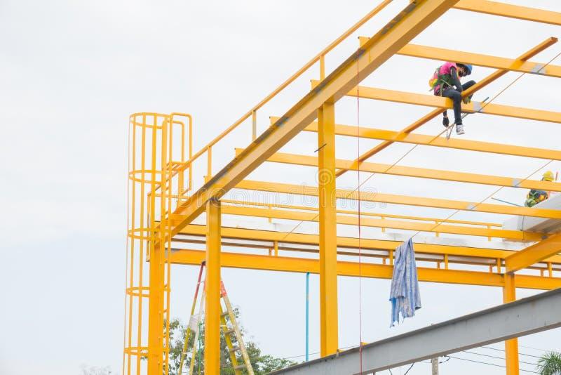 Arbeidskrachten die de gele structuur van het kleurenmetaal op dakbovenkant schilderen stock fotografie