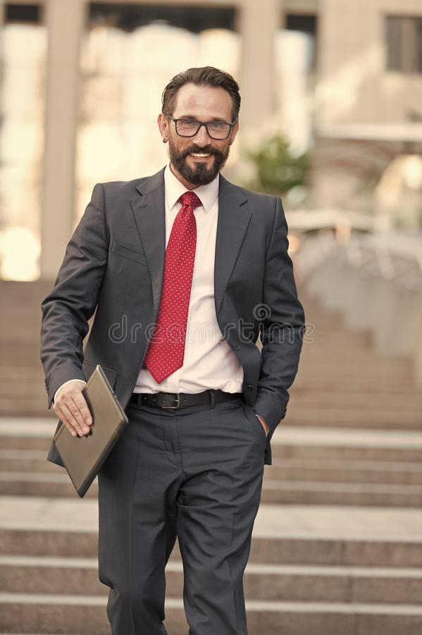 Arbeit über die Tablette Geschäftsmann geht hinunter die Straße, die eine Minitablette in seiner Hand hält Porträt von glückliche lizenzfreies stockfoto