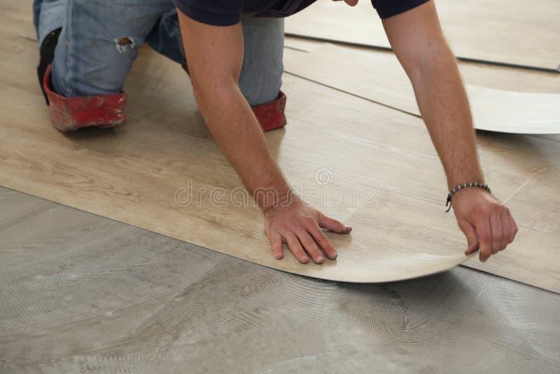 Arbeit über das Legen des Bodenbelags Arbeitskraft, die neuen Vinylfliesenboden installiert stockfotografie