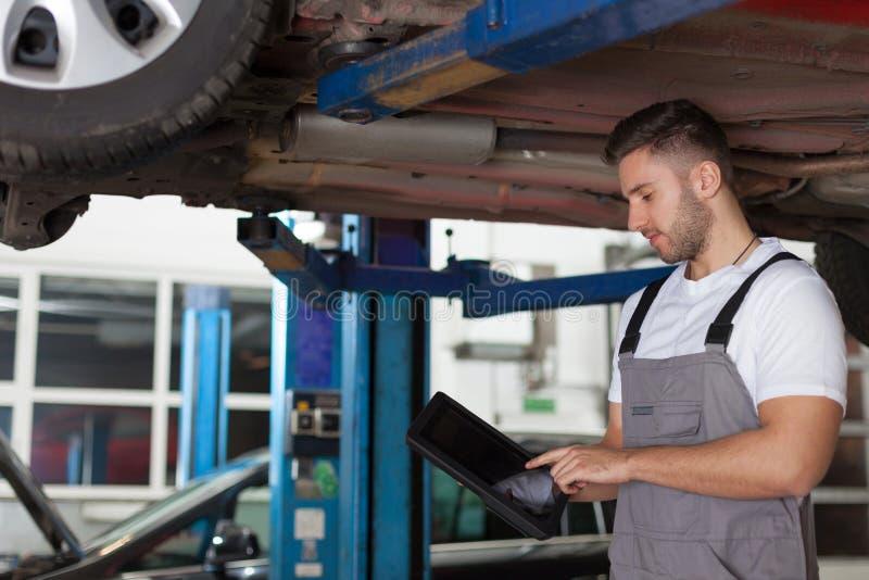 Arbeiten an einer digitalen Tablette unter dem Auto stockbild
