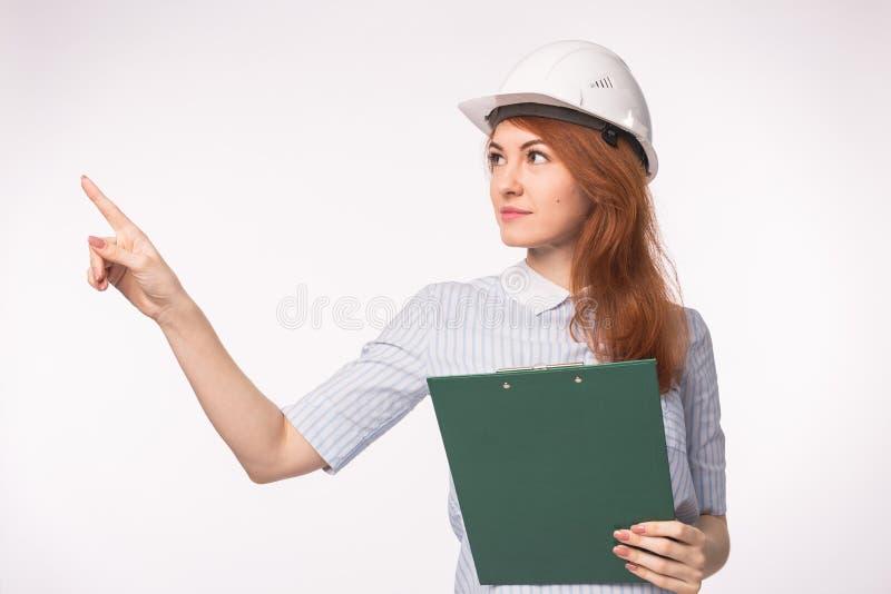 Arbeiten, führend, Leutekonzept - junges schönes Rothaarigemädchen im Architektensturzhelm aus stockbild